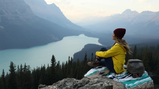 a woman sitting on a mountain top, taking in the view high above and alpine lake. - top garment stock videos & royalty-free footage