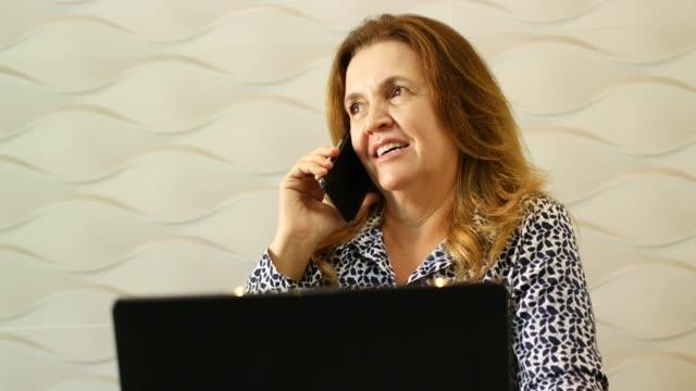 vídeos de stock, filmes e b-roll de mulher sentada em uma mesa de escritório usando laptop e falando por telefone. - 50 54 anos