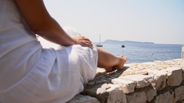 SLO MO に座る女性の桟橋の上の石