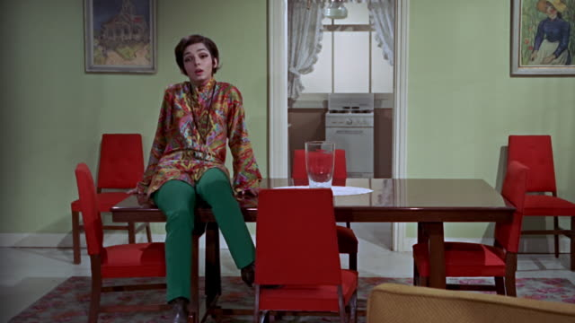 vídeos de stock, filmes e b-roll de woman sitting on a table surrounded by red chairs. her maid comes and they start talking. she is wearing vintage 1960s outfit. - 1960 1969