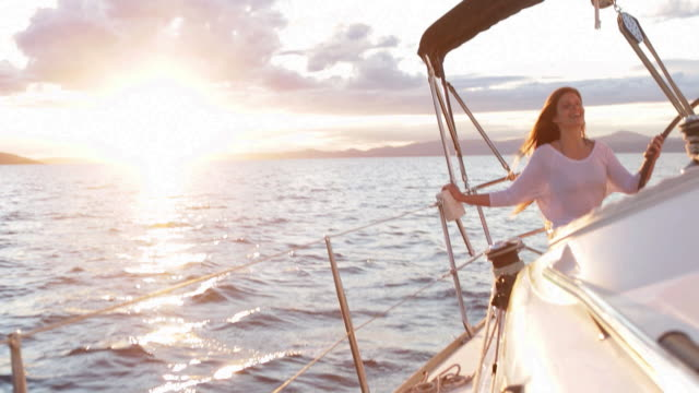 WS Woman sitting on back of yacht steering.