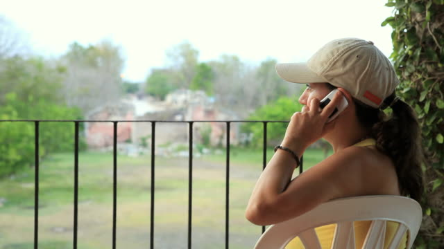MS Woman sitting on balcony talking on cell phone, Yucatan, Mexico
