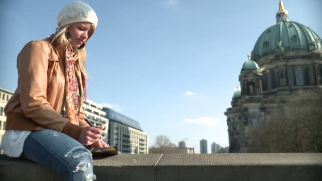 ms woman sitting on balustrade and writing journal infront of berlin cathedral / berlin, germany - newoutdoors stock videos & royalty-free footage