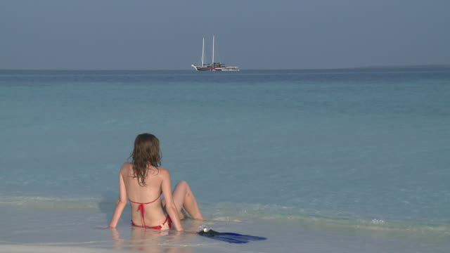 stockvideo's en b-roll-footage met woman sitting on beach in bikini, vaavu atoll, the maldives - duurzaam toerisme
