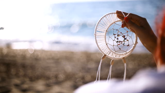 Woman sitting on beach sand with Dreamcatcher