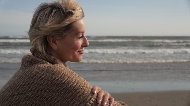 woman sitting on beach. - pullover stock videos & royalty-free footage