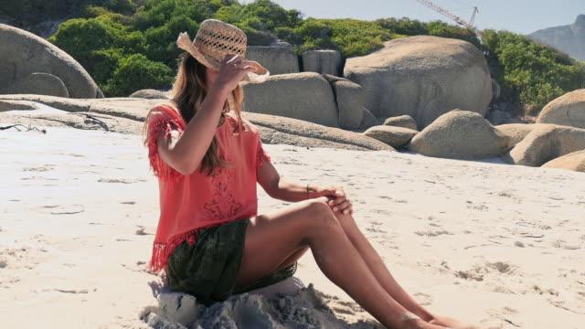 woman sitting on beach - sun hat stock videos & royalty-free footage