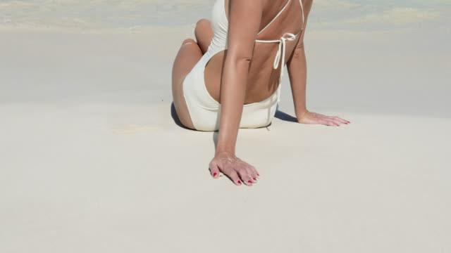 woman sitting on beautiful white sand beach back to camera - 水着点の映像素材/bロール