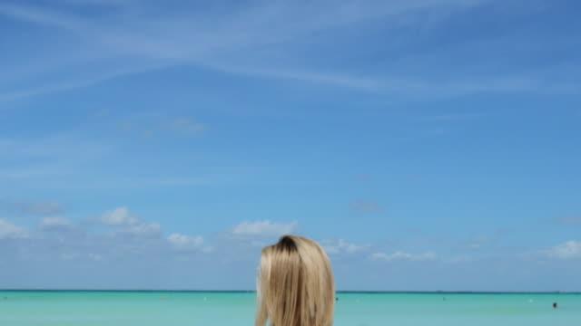 woman sitting on beautiful white sand beach back to camera - solo una donna di età media video stock e b–roll