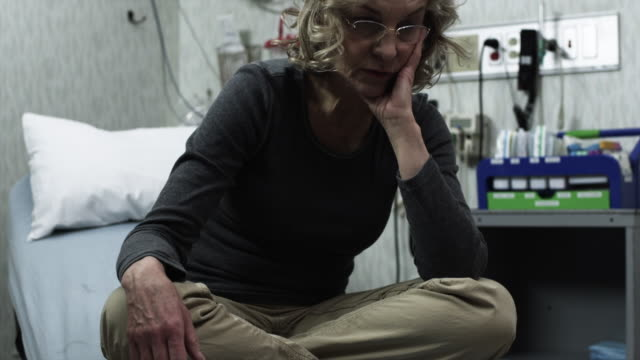 MS Woman sitting on bed in clinic / Payson, Utah, USA