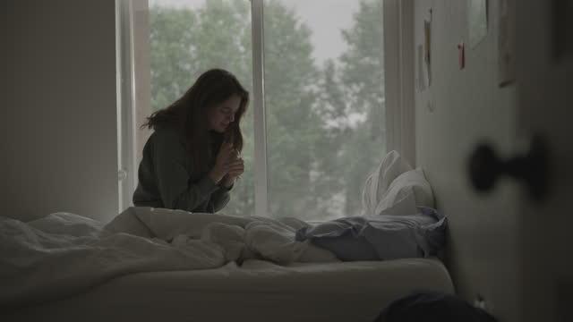 woman sitting on bed near window praying / provo, utah, united states - provo stock videos & royalty-free footage