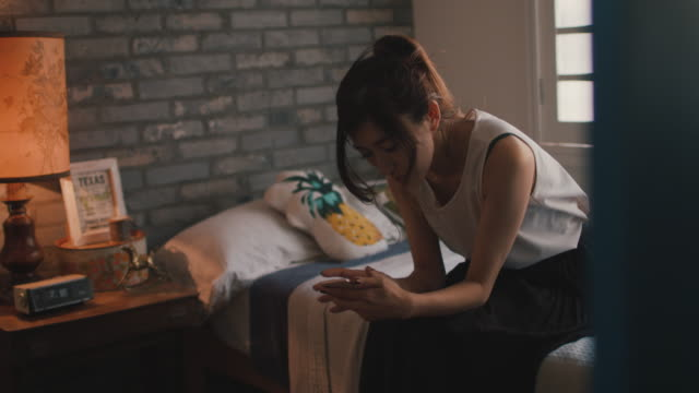 woman sitting on bed with cell phone typing in tokyo, japan. - portability点の映像素材/bロール