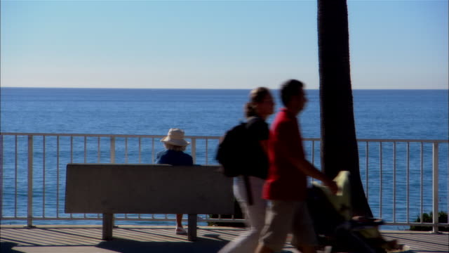 MS, Woman sitting on bench, facing ocean, rear view, people passing by in foreground, Carlsbad, California, USA