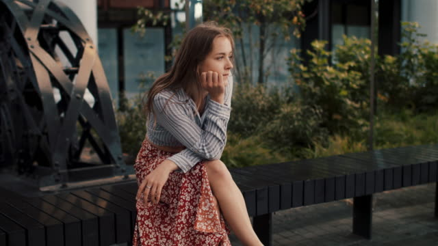 woman sitting on bench staring into distance - skirt stock videos & royalty-free footage