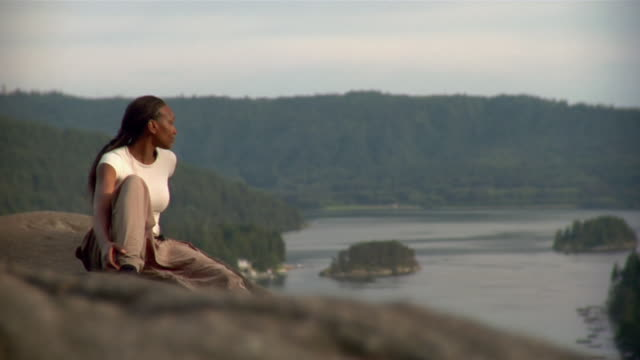 woman sitting on bluff and looking at view of lake - kelly mason videos stock-videos und b-roll-filmmaterial