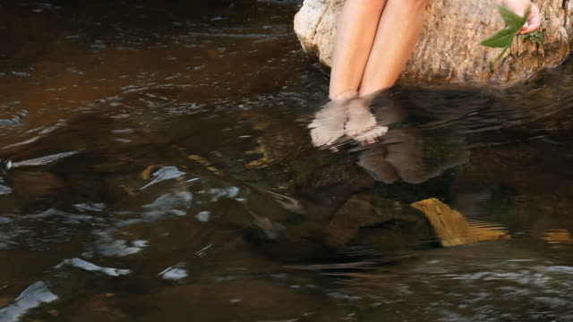 CU Woman sitting on boulder with feet in creek, low section, putting leaf into water, Sedona, Arizona, USA