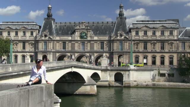 ms woman sitting on bridge near river seine / paris, ile-de-france, france     - ile de france stock videos and b-roll footage