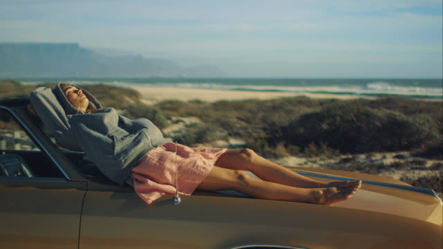 woman sitting on car at the beach - reclining stock videos & royalty-free footage