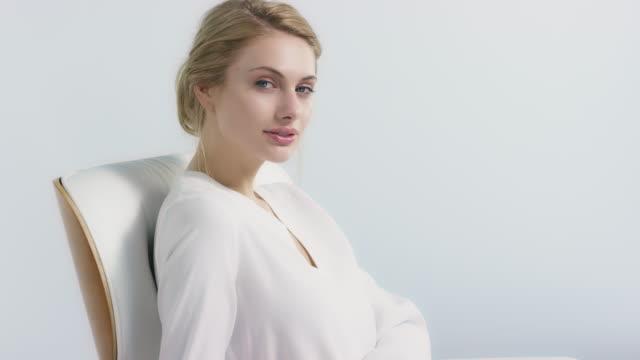vídeos de stock e filmes b-roll de woman sitting on chair against white background - higiene