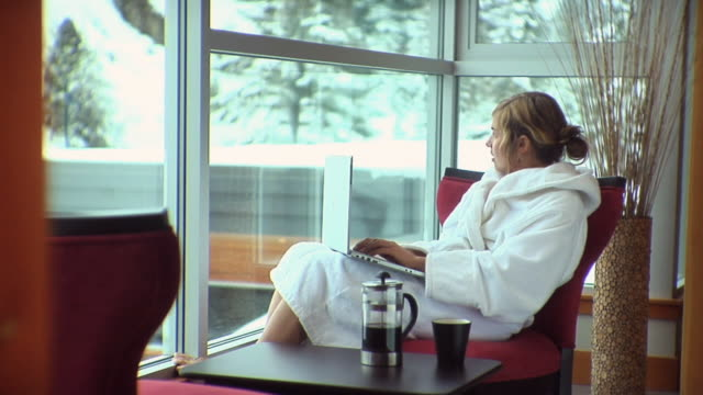 MS Woman sitting on chair by window using laptop, drinking coffee / Whistler, British Columbia, Canada