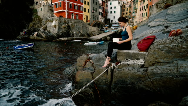 Woman sitting on Cinque Terre seaside  in Italy