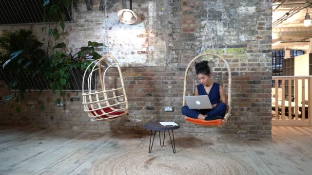 vídeos de stock e filmes b-roll de woman sitting on comfortable chair using laptop - de corpo inteiro