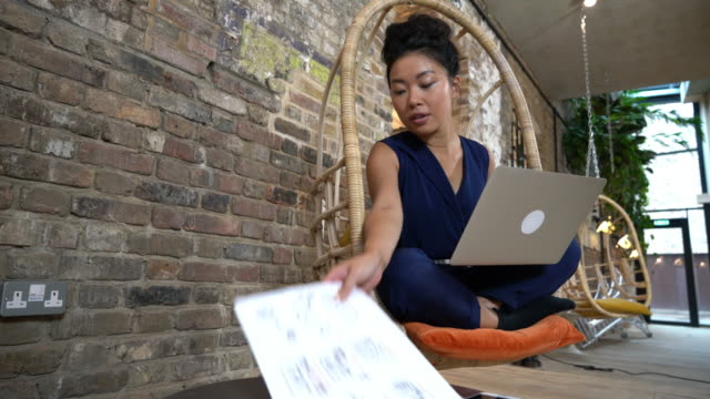 woman sitting on comfortable chair using laptop - reaching stock videos & royalty-free footage