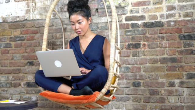 woman sitting on comfortable chair using laptop - cross legged stock videos & royalty-free footage