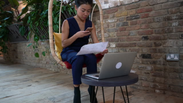 woman sitting on comfortable chair using laptop - smart casual stock videos & royalty-free footage