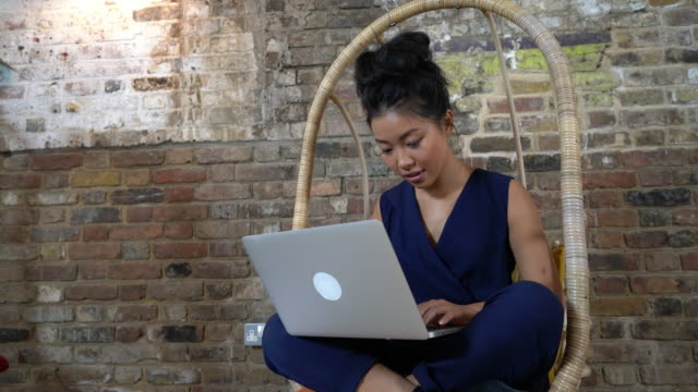 woman sitting on comfortable chair using laptop - chair stock videos & royalty-free footage