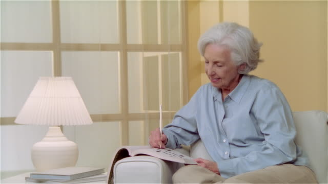 ms woman sitting on couch and doing crossword puzzle - crossword stock videos & royalty-free footage