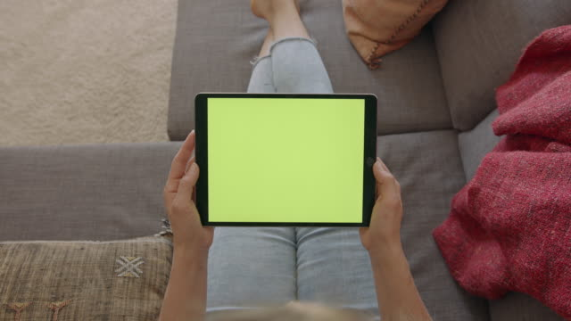 vidéos et rushes de woman sitting on couch holding digital tablet watching green screen - tablette numérique
