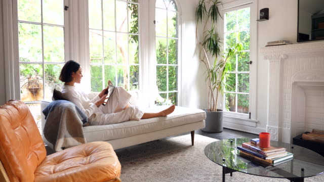 ws woman sitting on couch in living room reading on digital tablet - east asian ethnicity stock videos & royalty-free footage