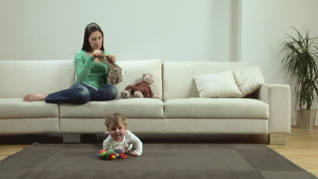 WS SLO MO Woman sitting on couch knitting, baby (6-11 months) lying on carpet / London, UK