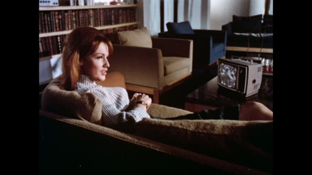 montage woman sitting on couch watching television / man pouring drink into glass / record playing on record player / united kingdom - 1965 stock videos & royalty-free footage