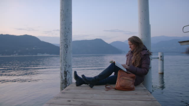 woman sitting on dock reads book at sunset, enjoys moment alone - animal skin stock videos & royalty-free footage