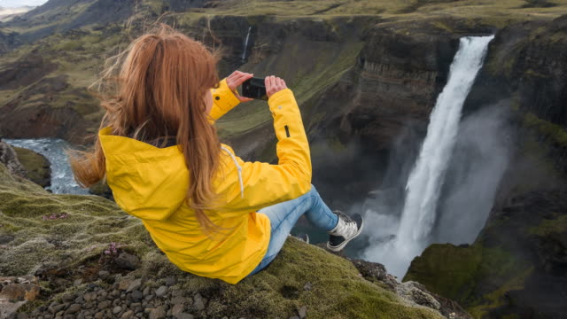 Woman sitting on edge of a canyon, taking pictures of waterfall