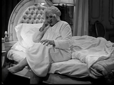 1937 b/w ms woman (trixie friganza) sitting on edge of bed and picking toes and nose before getting into bed and turning light off - bedtime stock videos & royalty-free footage
