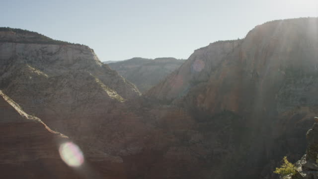woman sitting on edge of cliff overlooking the valley of a canyon - zion national park stock videos & royalty-free footage