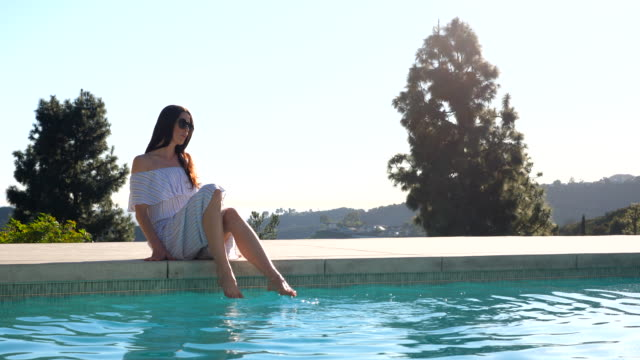 vidéos et rushes de ms woman sitting on edge of pool with feet in water - rebord de piscine