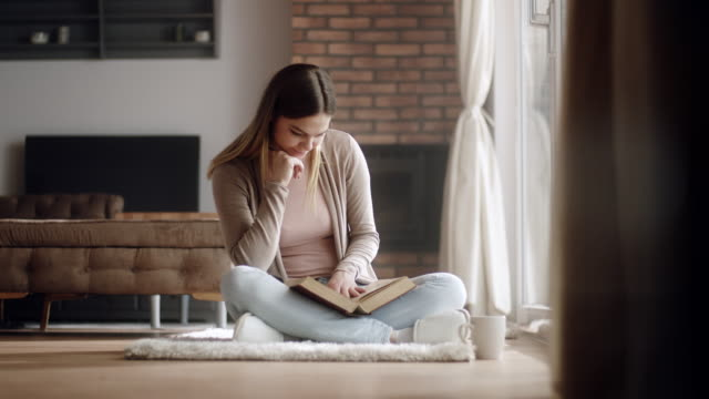 woman sitting on floor at living room, drinking coffee and reading a book - magazine publication stock videos & royalty-free footage