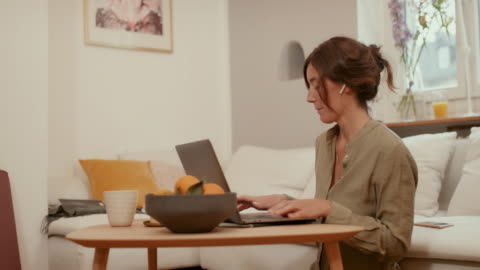 woman sitting on floor in living room typing on laptop - mid adult women stock videos & royalty-free footage