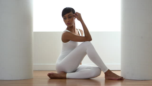woman sitting on floor in white singlet