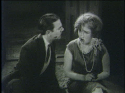 B/W 1926 woman sitting on floor slaps man with lipstick on cheek sitting on floor