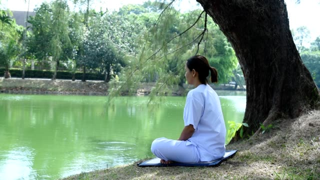 Woman sitting on green grass in a park beside the lake. Concept of calm and meditation.