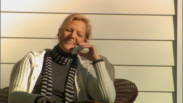 MS Woman sitting on in wicker chair on porch and answering mobile phone/ Livingston, New York