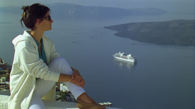 WS Woman sitting on ledge and looking at scenic view of islands / Santorini, Greece