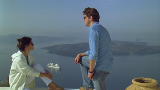 WS Woman sitting on ledge and looking at scenic view of islands, then man joins her / Santorini, Greece