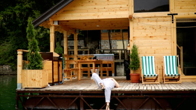 woman sitting on log cabin pier - balcony - capanna di legno video stock e b–roll