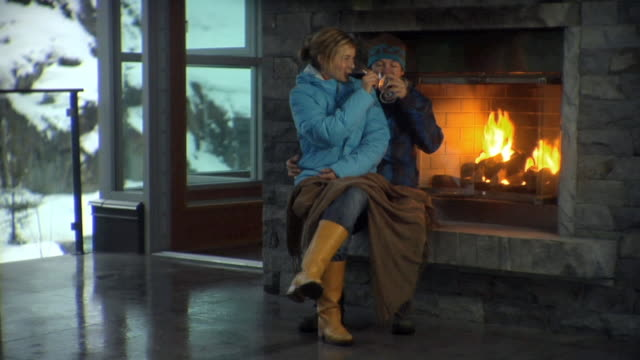 WS Woman sitting on man's lap beside fireplace and having drink / Whistler, British Columbia, Canada